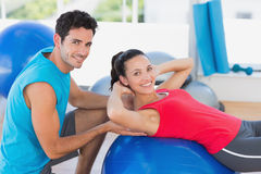 Male trainer helping woman with her exercises. Portrait of a male trainer helping women with her exercises at a bright gym Royalty Free Stock Image