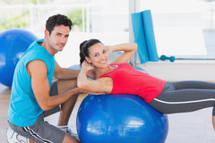Male trainer helping woman with her exercises. Portrait of a male trainer helping women with her exercises at a bright gym Stock Image