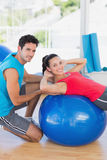 Male trainer helping woman with her exercises. Portrait of a male trainer helping women with her exercises at a bright gym Royalty Free Stock Photography