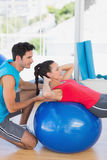 Male trainer helping woman with her exercises. Side view of a male trainer helping women with her exercises at a bright gym Stock Photography