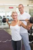 Male trainer helping woman with lifting barbell in gym. Personal male trainer helping young women with lifting barbell in the gym Stock Images