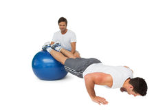 Male trainer helping young man exercise on fitness ball. Male trainer helping young men exercise on fitness ball over white background Stock Photography