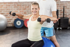 Male trainer helping young woman with the dumbbells. Male trainer helping young women with the dumbbells in crossfit gym Stock Photos