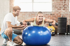 Male trainer helping young woman with the dumbbells. Male trainer helping young women with the dumbbells in crossfit gym Royalty Free Stock Photos