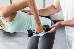 Male trainer helping young woman with the dumbbells. Male trainer helping young women with the dumbbells in crossfit gym Royalty Free Stock Image