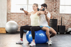 Male trainer helping young woman with the dumbbells. Male trainer helping young women with the dumbbells in crossfit gym Royalty Free Stock Photography