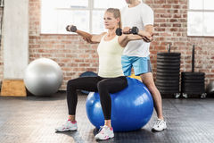 Male trainer helping young woman with the dumbbells. Male trainer helping young women with the dumbbells in crossfit gym Royalty Free Stock Images