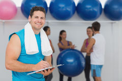 Male trainer holding clipboard with fitness class in background. Portrait of a male trainer holding clipboard with fitness class in background at the gym Stock Image