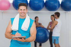Male trainer holding clipboard with fitness class in background Royalty Free Stock Image