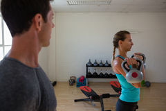 Male trainer looking at female athlete lifting kettlebells. At gym Royalty Free Stock Images