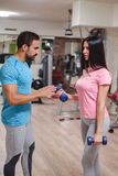Male trainer seriously train girl biceps with dumbbells Royalty Free Stock Photo