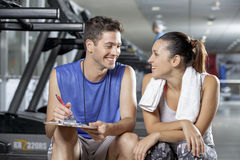 Male trainer sitting in gym with client. Trainer discussing a women client's workout schedule Stock Photos