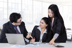 Male trainer speaking with employees. Young caucasian businessman talking a job with his partners in a meeting at office Royalty Free Stock Image