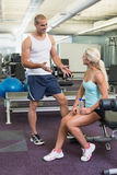 Male trainer talking to fit woman at gym. Smiling male trainer talking to fit young women at the gym Royalty Free Stock Photos