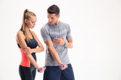 Male trainer teaching woman how to working with dumbbells. Portrait of a male trainer teaching women how to working with dumbbells isolated on a white background Stock Photos