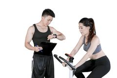 Male trainer timing his client during using a bicycle. Picture of male trainer timing his client during use an exercise bike in the studio, isolated on white royalty free stock image