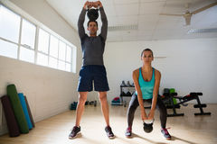 Male trainer training woman in lifting kettle bells at gym Stock Image