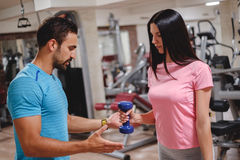 Male trainer trains girl brachioradialis with dumbbell. Gym indoors royalty free stock image