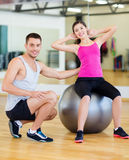 Male trainer with woman doing crunches on the ball. Fitness, sport, training, gym and lifestyle concept - male trainer with women doing crunches on the ball Stock Photos