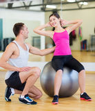Male trainer with woman doing crunches on the ball. Fitness, sport, training, gym and lifestyle concept - male trainer with women doing crunches on the ball Royalty Free Stock Photography