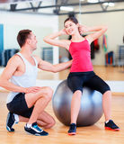 Male trainer with woman doing crunches on the ball Royalty Free Stock Photography