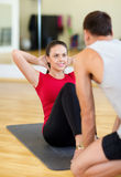 Male trainer with woman doing sit ups in the gym. Fitness, sport, training, gym and lifestyle concept - male trainer with women doing sit ups Stock Image