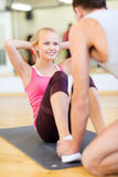 Male trainer with woman doing sit ups in the gym. Fitness, sport, training, gym and lifestyle concept - male trainer with women doing sit ups Stock Photography
