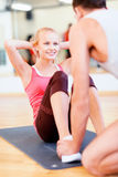 Male trainer with woman doing sit ups in the gym. Fitness, sport, training, gym and lifestyle concept - male trainer with women doing sit ups Stock Photo