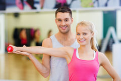 Male trainer with woman working out with dumbbell. Fitness, sport, training, gym and lifestyle concept - male trainer with women working out with dumbbell Royalty Free Stock Image