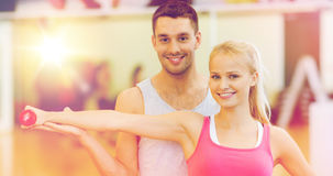 Male trainer with woman working out with dumbbell. Fitness, sport, training, gym and lifestyle concept - male trainer with women working out with dumbbell Royalty Free Stock Photos