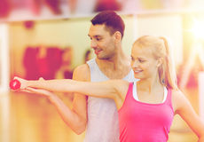 Male trainer with woman working out with dumbbell. Fitness, sport, training, gym and lifestyle concept - male trainer with women working out with dumbbell Stock Photos