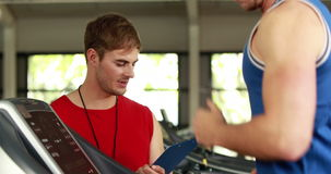 Male trainer writing about treadmill performance. In crossfit gym stock video footage