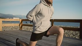 Male is training his legs near sea, doing squats with lunges, close-up stock video