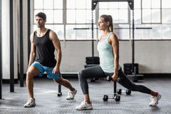 Male trainor with woman using dumbbells exercising. Male trainor with women using dumbbells exercising in crossfit gym Royalty Free Stock Photo