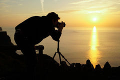 Male travel landscape photographer taking pictures of the view s. Unset with camera Royalty Free Stock Photo
