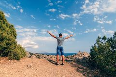 Male traveler with arms raised to the sky. In the rest Royalty Free Stock Image