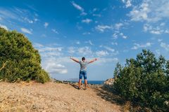 Male traveler with arms raised to sky on top of mountain. Male traveler with arms raised to the sky on top of a mountain Stock Photo