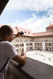 Male traveler on the background of Arcades in Wawel Castle in Cracow. Poland. Renaissance. A man takes photos on his mobile phone from the second floor of the Royalty Free Stock Image
