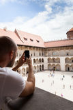 Male traveler on the background of Arcades in Wawel Castle in Cracow. Poland. Renaissance. A man takes photos on his mobile phone from the second floor of the Royalty Free Stock Images