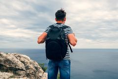 Male traveler with a backpack on her back looking at the sea. On vacation on top of a mountain Stock Photography