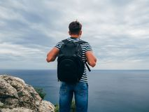 Male traveler with a backpack on her back standing on sea background summer nature. Symbolizes freedom Stock Photo