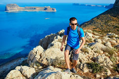 Male traveler with backpack runs on the cliff against sea and blue sky. At early morning. Balos beach on background, Crete, Greece Stock Photos