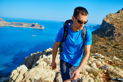 Male traveler with backpack runs on the cliff against sea and blue sky. At early morning. Balos beach on background, Crete, Greece Stock Images
