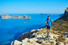 Male traveler with backpack runs on the cliff against sea and blue sky. At early morning. Balos beach on background, Crete, Greece Royalty Free Stock Image