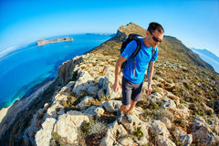 Male traveler with backpack runs on the cliff against sea and blue sky. At early morning. Balos beach on background, Crete, Greece Royalty Free Stock Photo