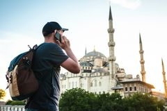 Male traveler with a backpack talking on a mobile phone near the blue mosque - the famous tourist attraction of Istanbul. Travel, tourism Royalty Free Stock Photo