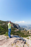Male traveler enjoying the views from the mountains of Montserrat in Spain and makes a photo Royalty Free Stock Photography