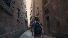 Young man is walking alone in dark narrow street in Gothic Quarter in Barcelona. Male traveler is exploring old medieval buildings strolling on narrow street. He stock footage