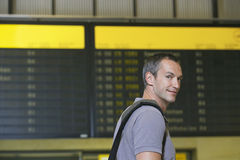 Male Traveler In Front Of Flight Status Board Royalty Free Stock Photos