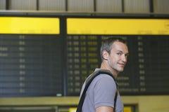 Male Traveler In Front Of Flight Status Board. Closeup of a smiling male traveler in front of flight status board in airport Royalty Free Stock Photos